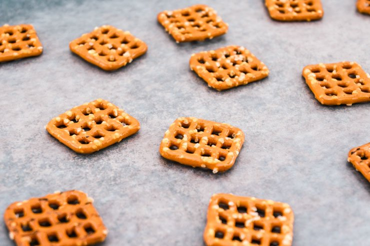 lay out pretzel squares on cookie sheet