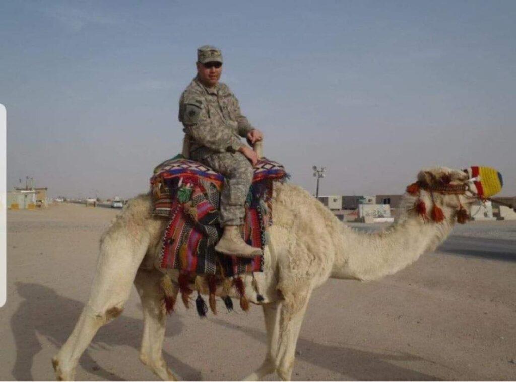 Family member riding on camel in desert, for DAV Vehicle Program post